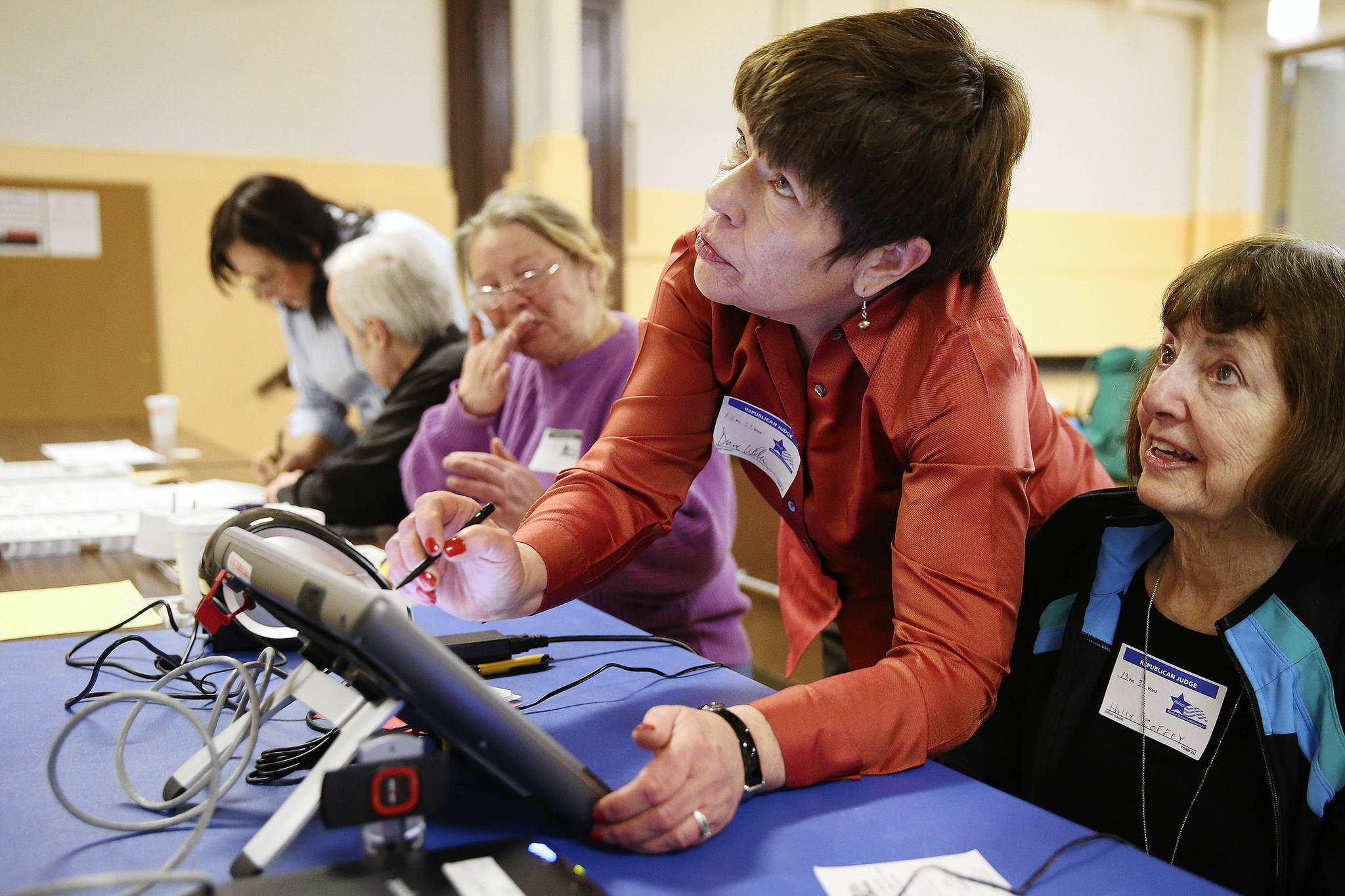 Election judge Diane Wilber, second from right, checks an electronic poll book for a voter shortly after the polls opened on Tuesday at Carlos Fuentes charter school in the Avondale neighborhood of Chicago. At right is election judge Holly Coffey.
