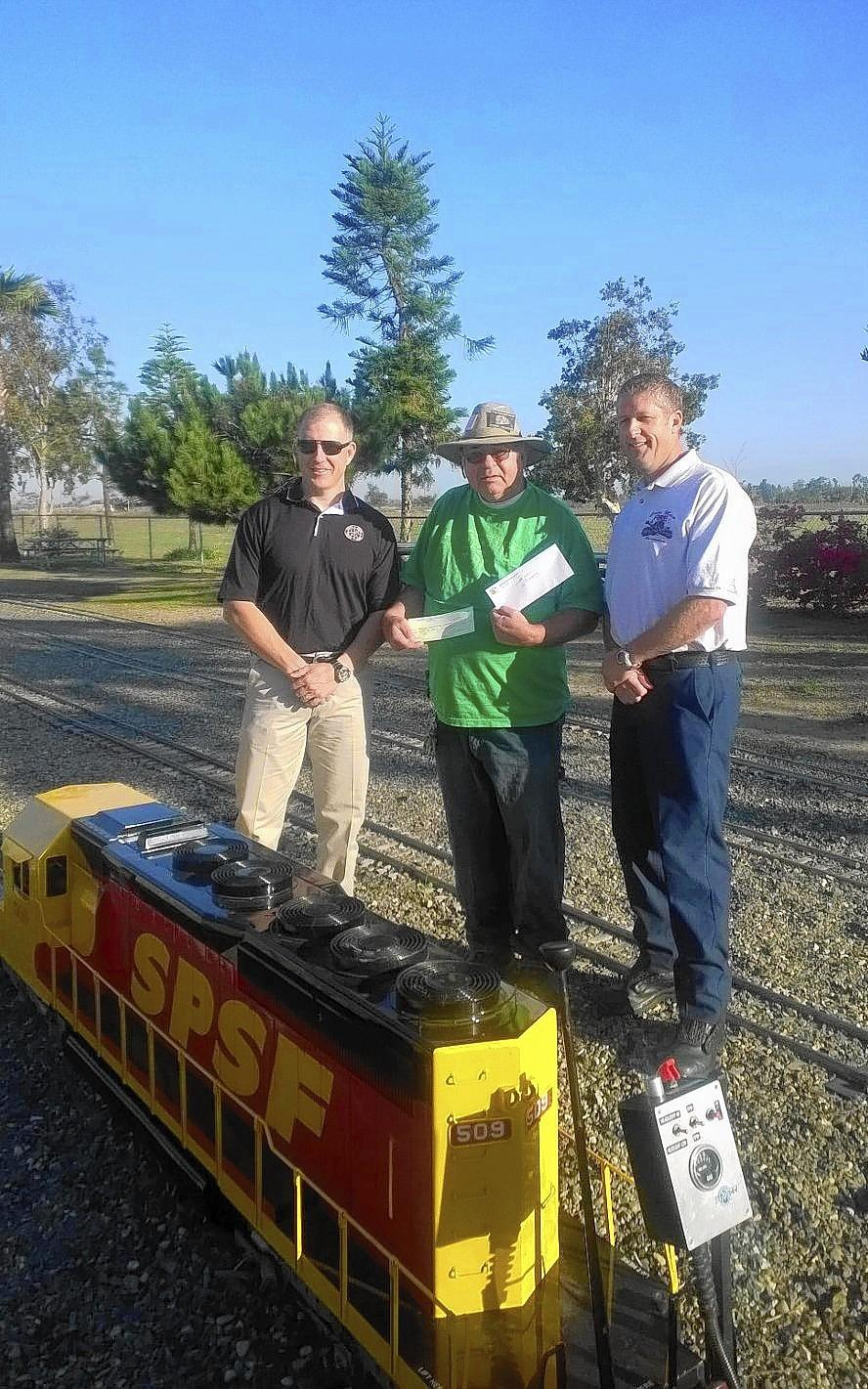 Orange County Model Engineers Vice President of Operations Dixon Sheldon, center, stands with Rob Dimel, left, and Rob Gagne. Dimel, of the Costa Mesa Police Assn., and Gagne, of the Costa Mesa Firefighters Assn., each presented the nonprofit club with a $500 donation Sunday.