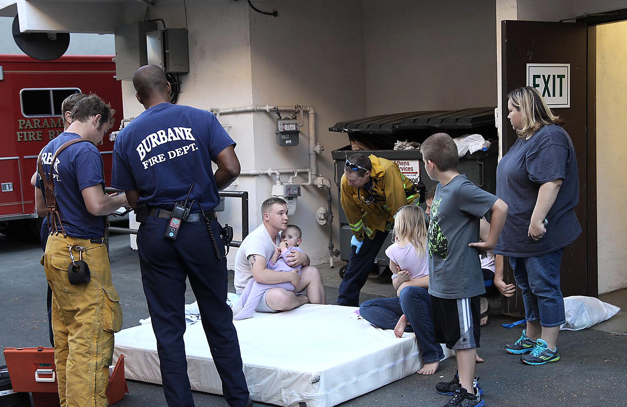 Firefighters examine a 3-year-old boy who fell out of a third-story window and was caught by Konrad and Jennifer Lightner on a mattress they were moving in the 4100 block of Kling Street in Burbank on Sunday, March 16, 2014.