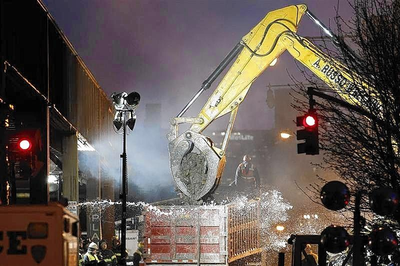 An excavator clears debris at the site of a building explosion in the Harlem section of New York