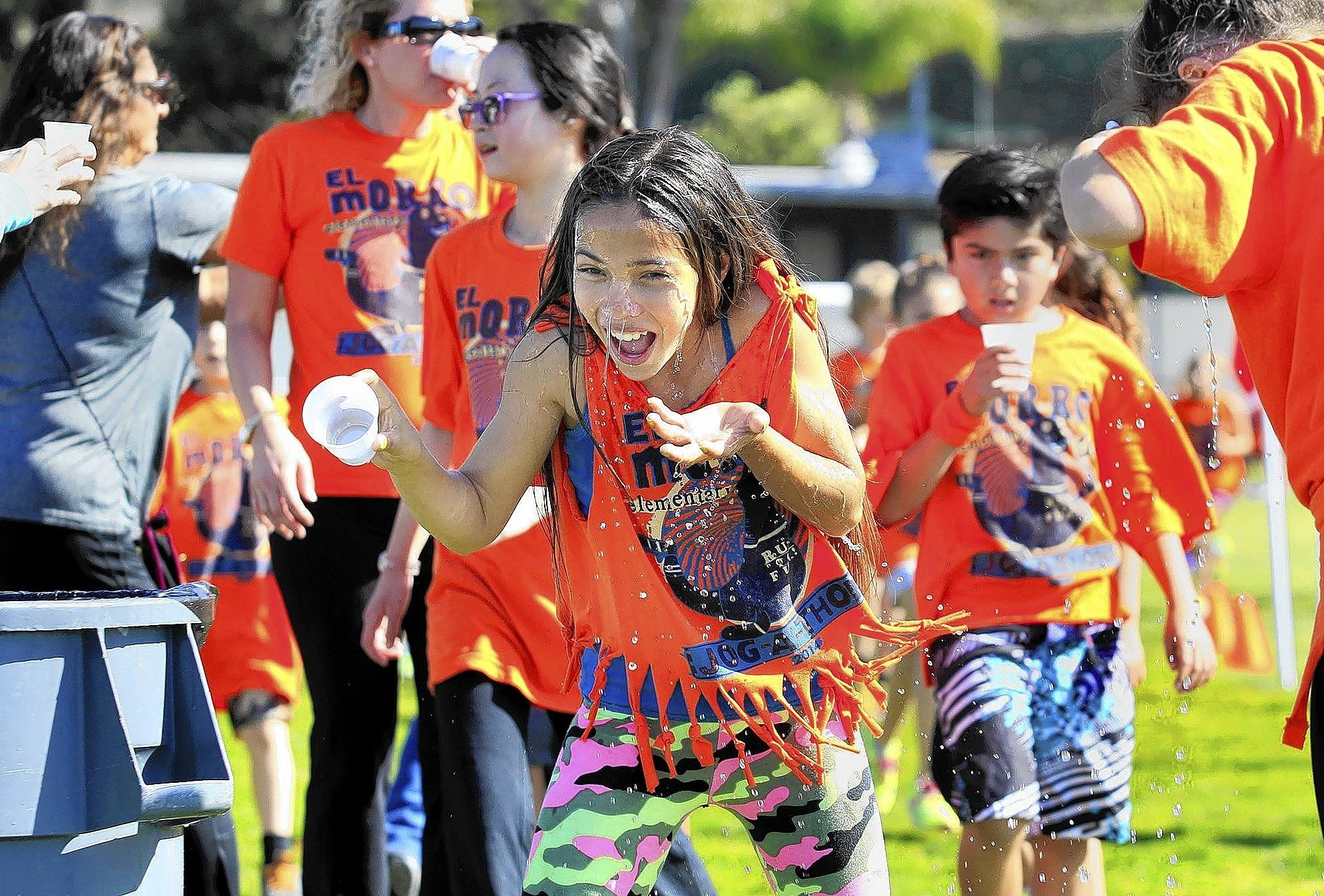 Fourth-grader Makena Angus, 10, dumps a cup of water on her face as she participates in the annual Jog-A-Thon fundraiser at El Morro Elementary on Friday.