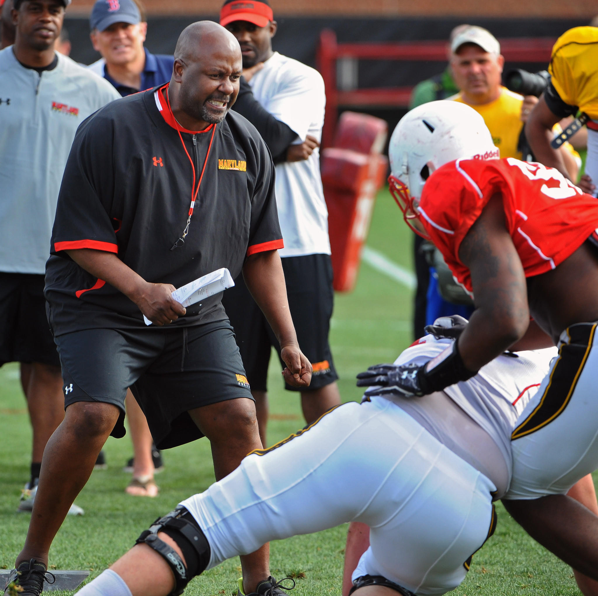 Maryland offensive coordinator Mike Locksley watches blocking drills during the team's spring practice in 2012.