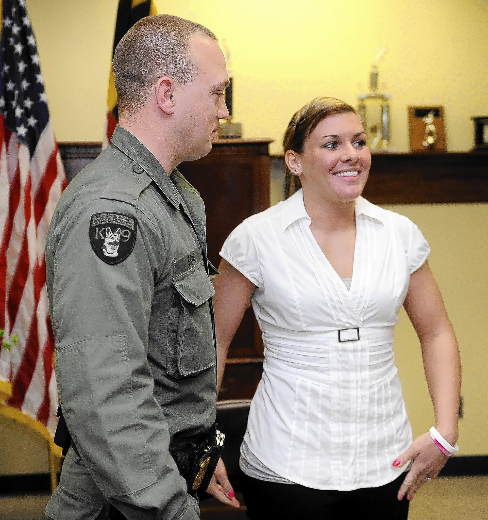 Maryland State Trooper First Class Jacqueline Kline, right, stands with Trooper First Class Justin Fohs, left. TFC Kline was injured in October when she was hit by a car during a traffic stop while backing up TFC Fohs. She said she credits his quick thinking and actions with saving her life.