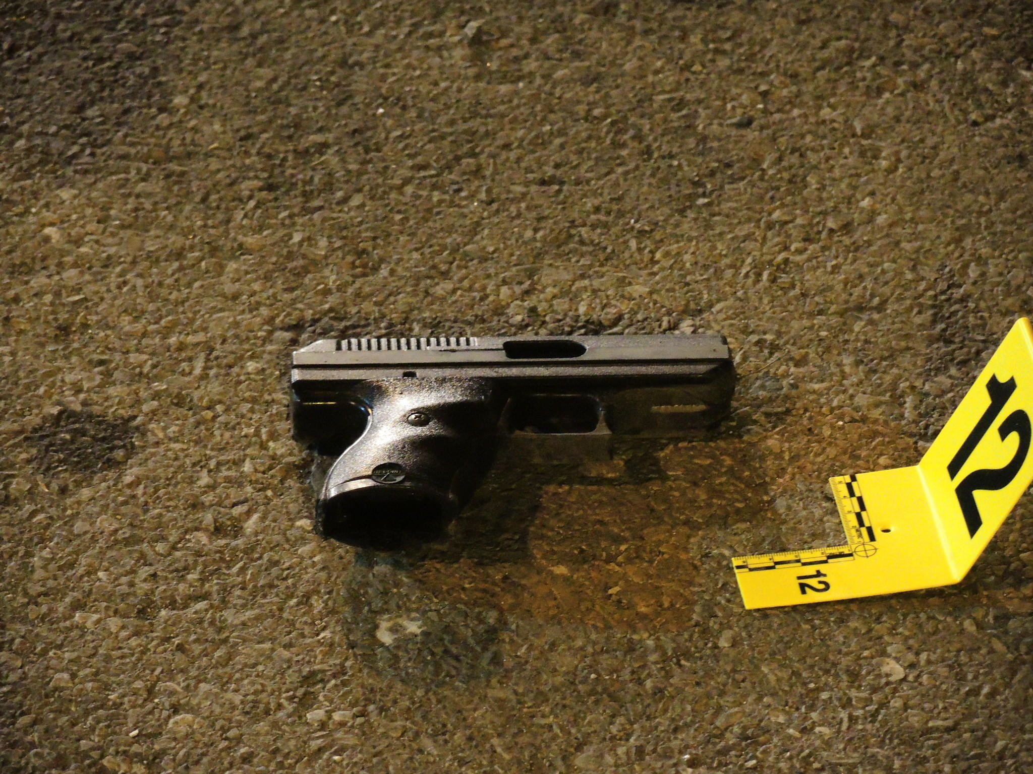 A .380 handgun tossed from the suspects' vehicle during a chase is marked as evidence.