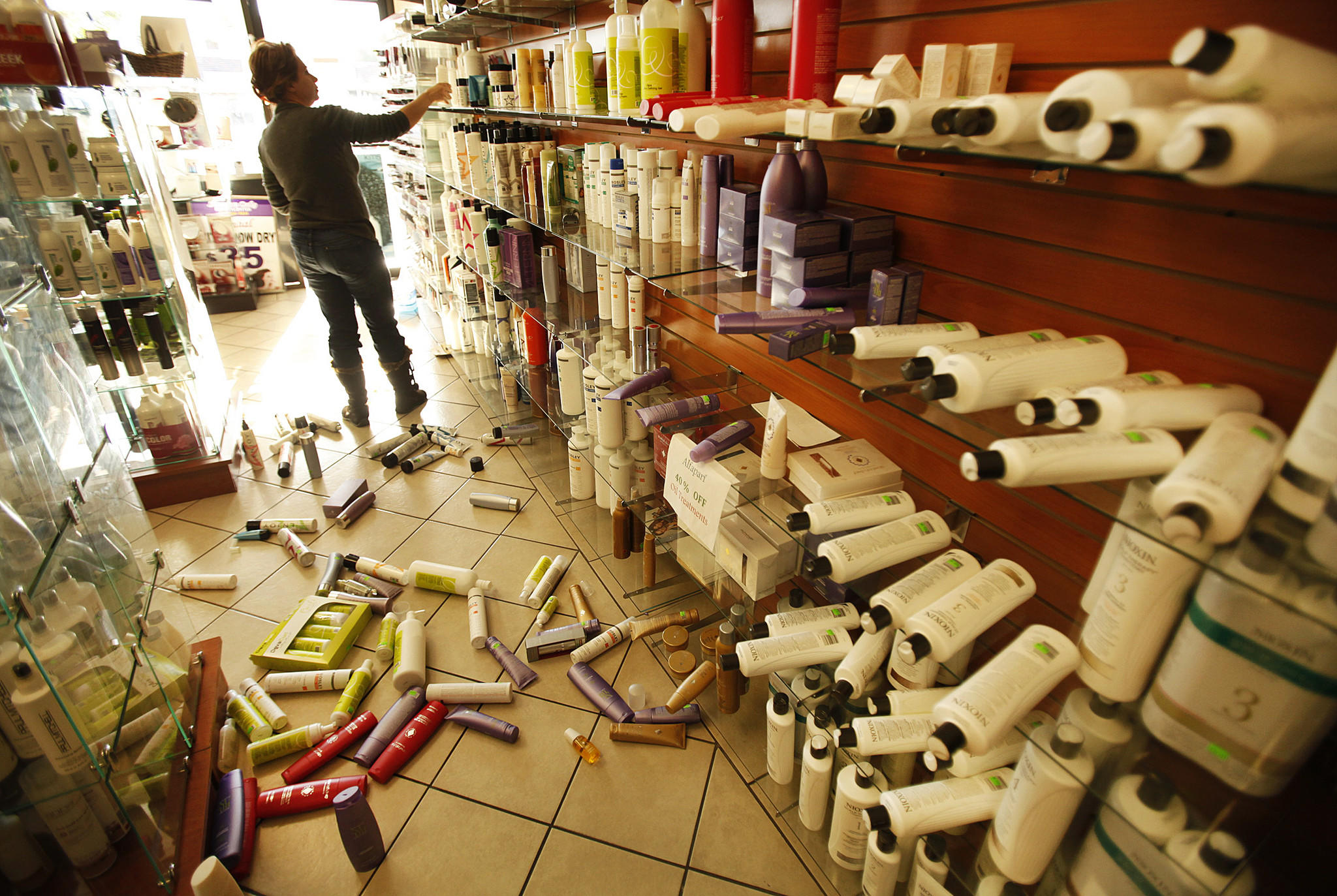 Roya Alagh, manager of Sherman Oaks Beauty Center, cleans up merchandise knocked from store shelves by a magnitude 4.4 earthquake that struck Los Angeles about 6:25 a.m. Monday.
