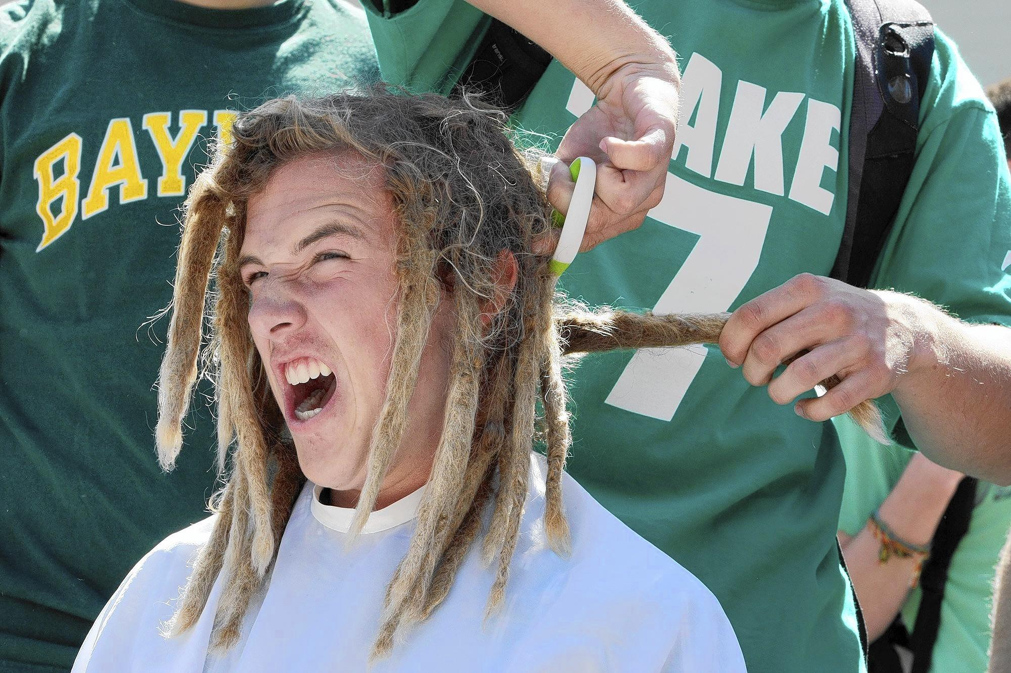 Griffin Van Amringe reacts as his dreadlocks are cut. Teachers and students at La Cañada High School shaved their heads for in support of pediatric cancer awareness and LCHS student Melissa Leo, who was recently diagnosed with leukemia, during the St. Baldrick's Day event on Monday, March 17, 2014.
