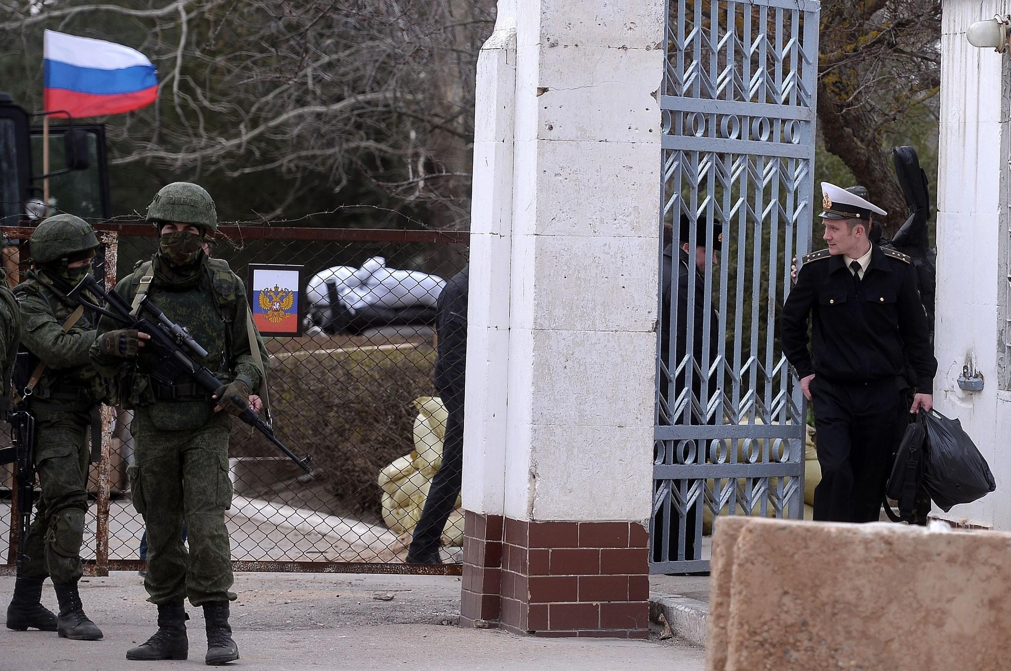 A Ukrainian officer, right, leaves a base in the Crimean city of Novoozerne after it was taken by Russian forces.