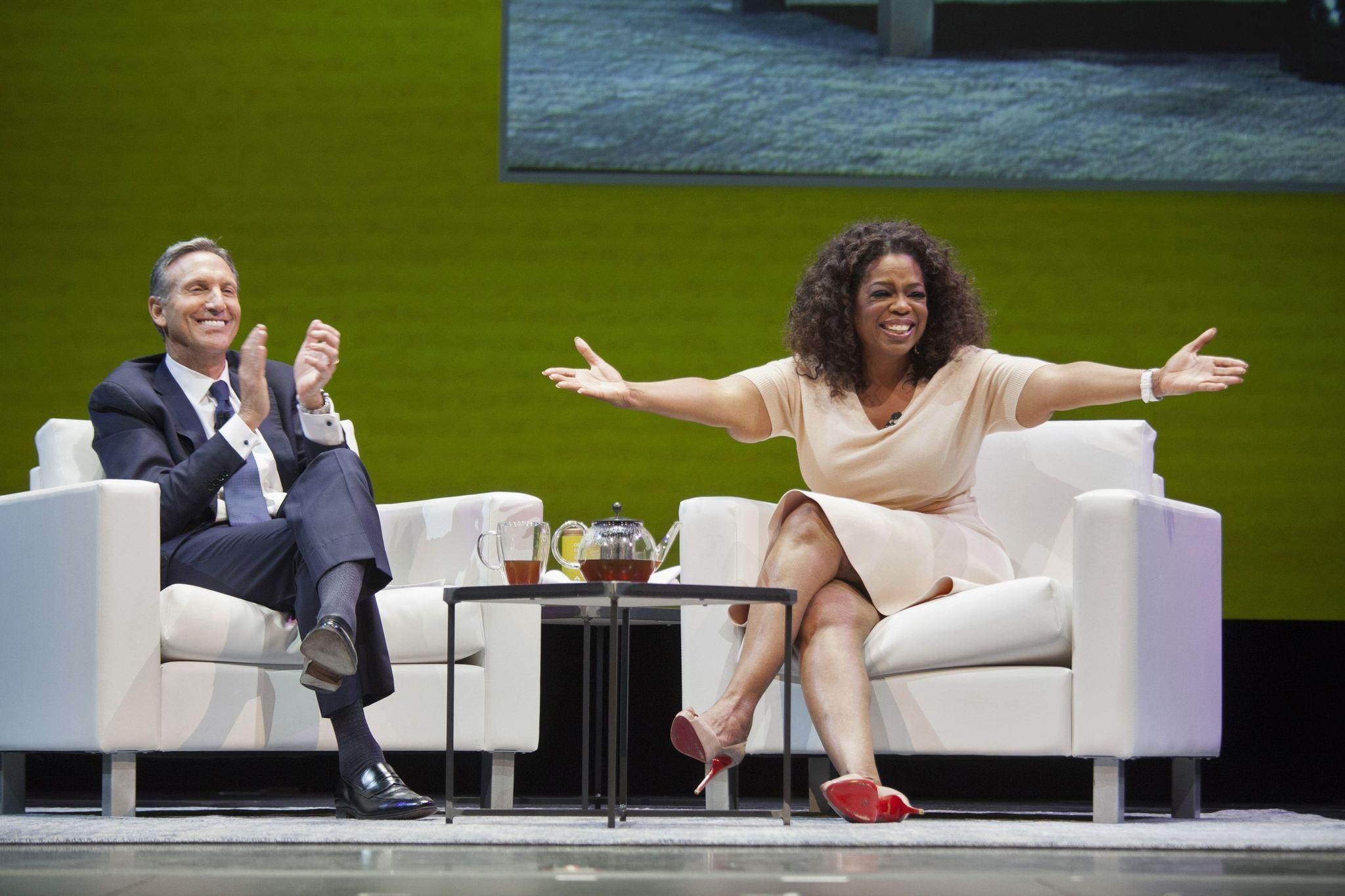Howard Schultz, CEO of Starbucks, applauds on stage next to surprise guest Oprah Winfrey during the company's annual shareholders meeting in Seattle, Washington on March 19.