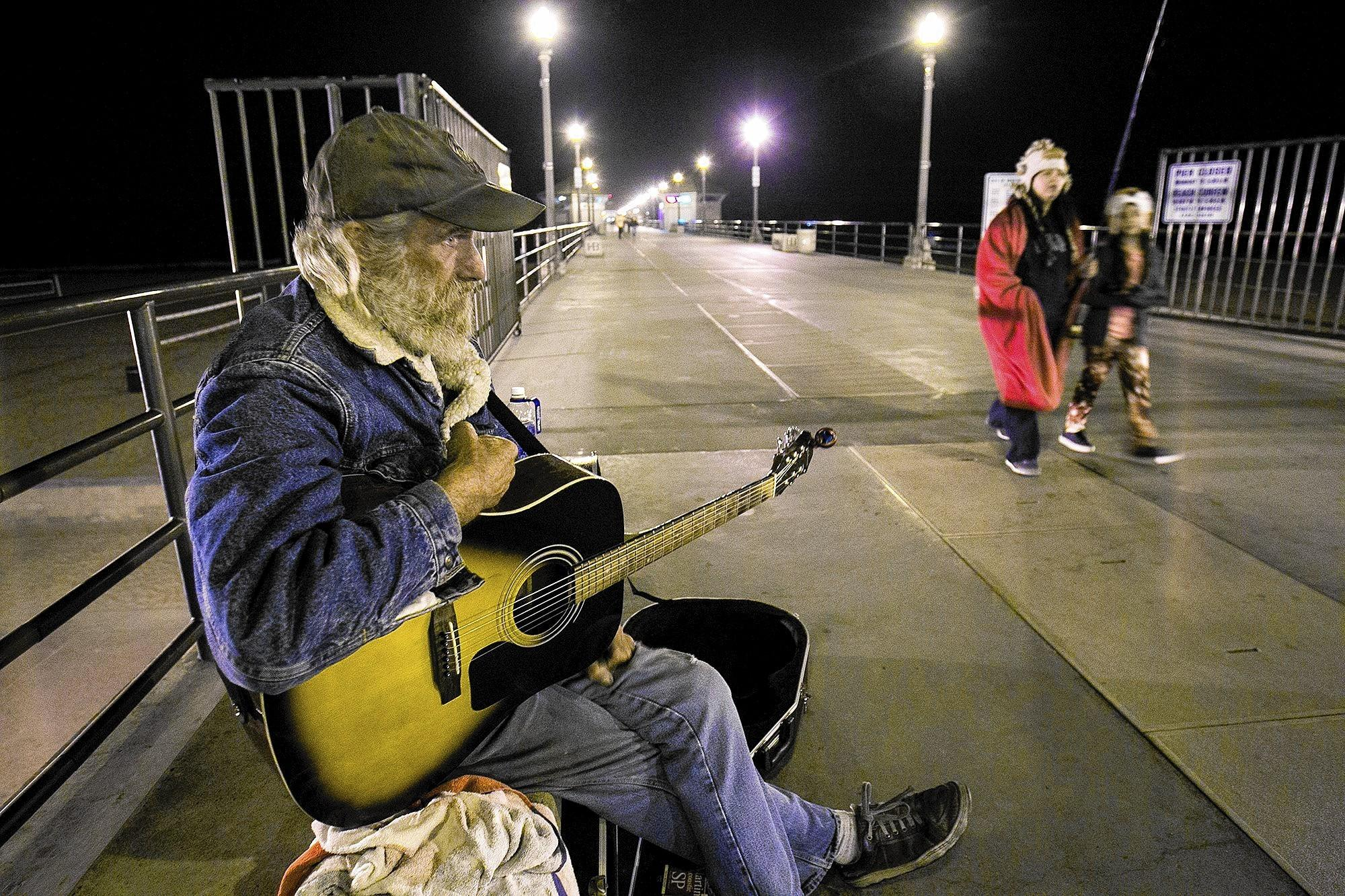 Mike Carltock plays guitar on the Huntington Beach Pier on Tuesday night. Carltock, who is homeless, lives out of his truck and survives on Social Security and the tips he makes playing guitar.