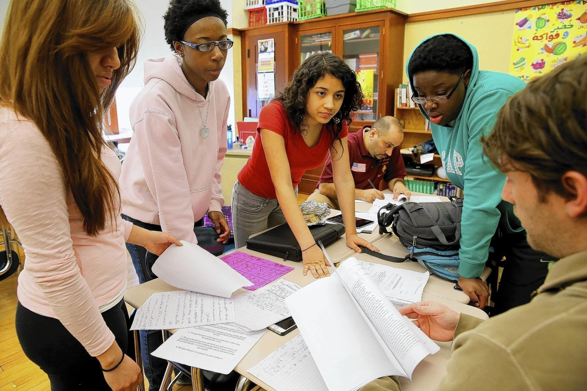 Karina Reyes, 17, from left, LaCharro Hawkins, 18, Brenda Macias, 15, Erin Nwachukwu, 15, and teacher Tyler Blackwell prepare for their debate and trip to Doha, Qatar, after classes at Robert Lindblom Math and Science Academy in Chicago.