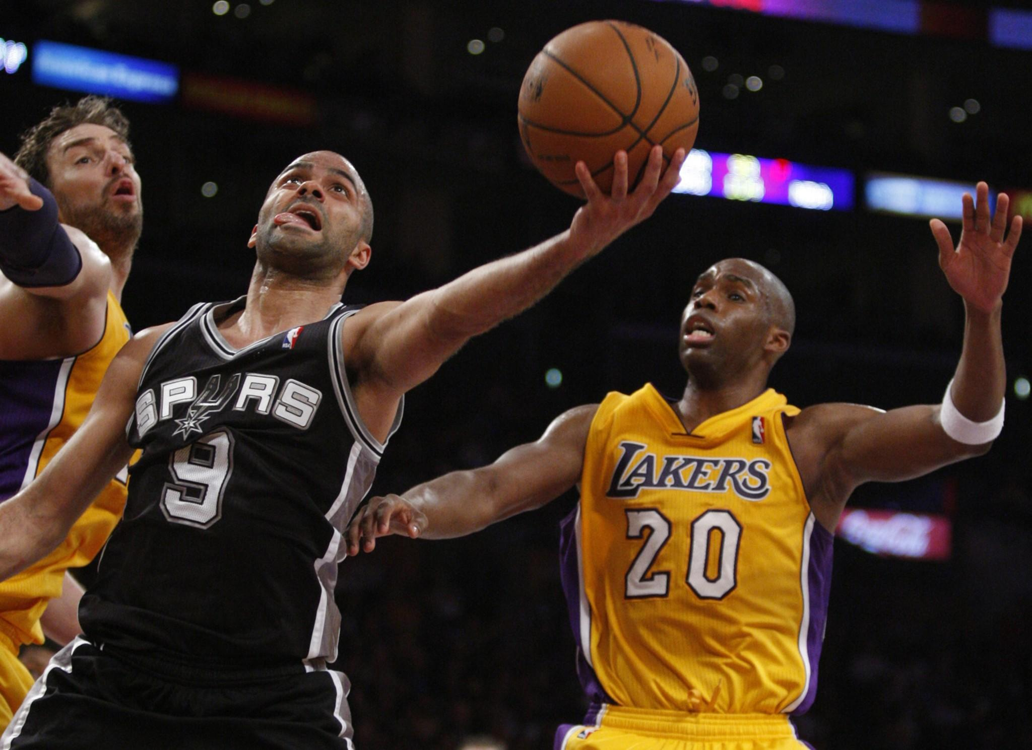Spurs point guard Tony Parker gets past Lakers power forward Pau Gasol, left, and guard Jodie Meeks for a layup.