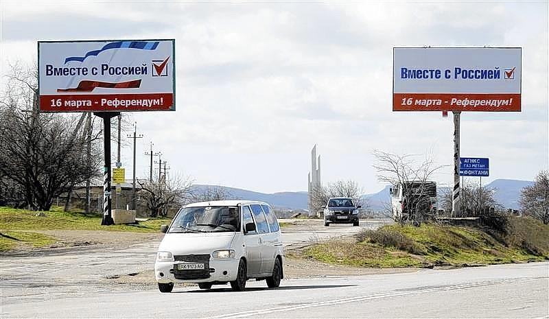 """A car drives near referendum billboard posters that reads """"Together with Russia; 16 March - Referendum"""" in Simferopol."""