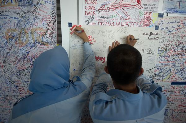 Students write on a placard carrying messages for the passengers of missing Malaysia Airlines flight MH370 at Kuala Lumpur International Airport.