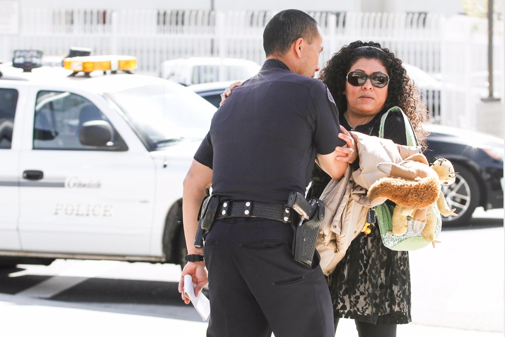 While Glendale Police Officer Stan Mar interviews a witness, she reenacts how a suspect may have stabbed a woman at Pacific Avenue and San Fernando Road on Thursday.