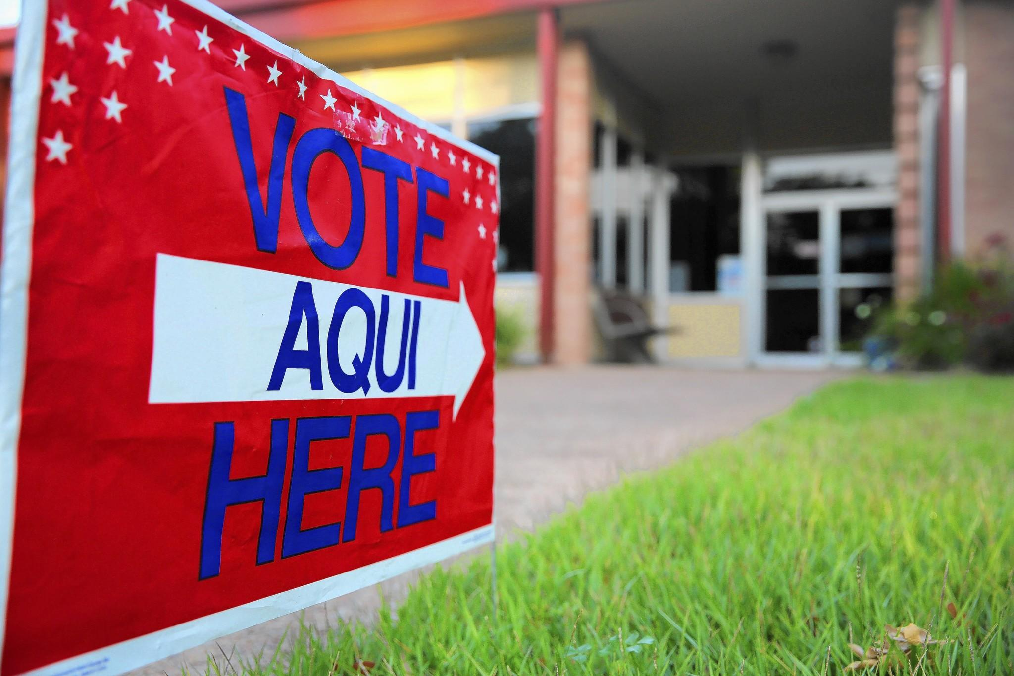 A bilingual sign points to a polling station in Austin, Texas, last year. Republicans in Texas and Florida have had success wooing Latinos, but that's not the case elsewhere.
