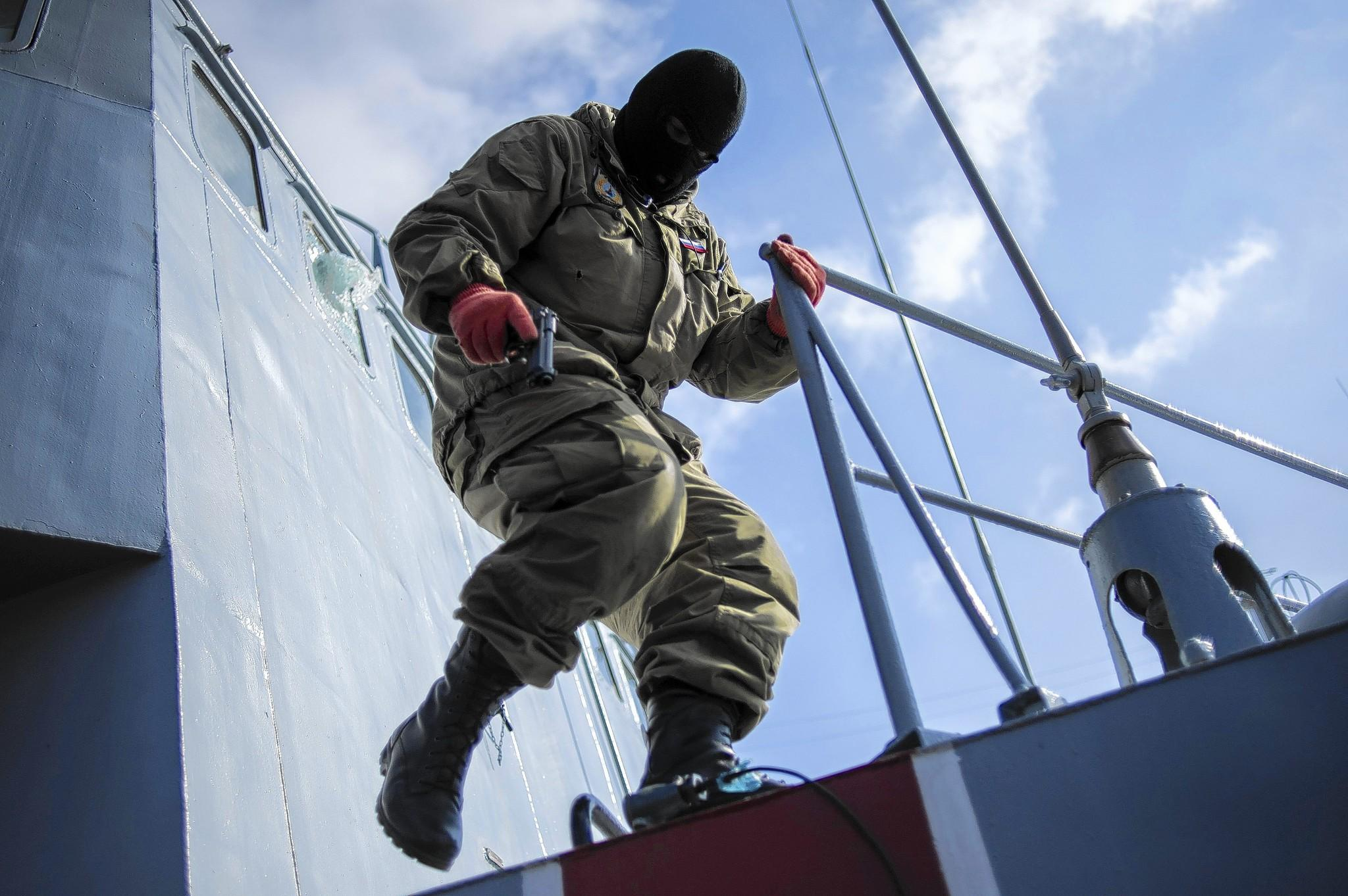 A member of a pro-Russia self-defense force holds a gun during the seizure of a Ukrainian warship in Sevastopol, Crimea.