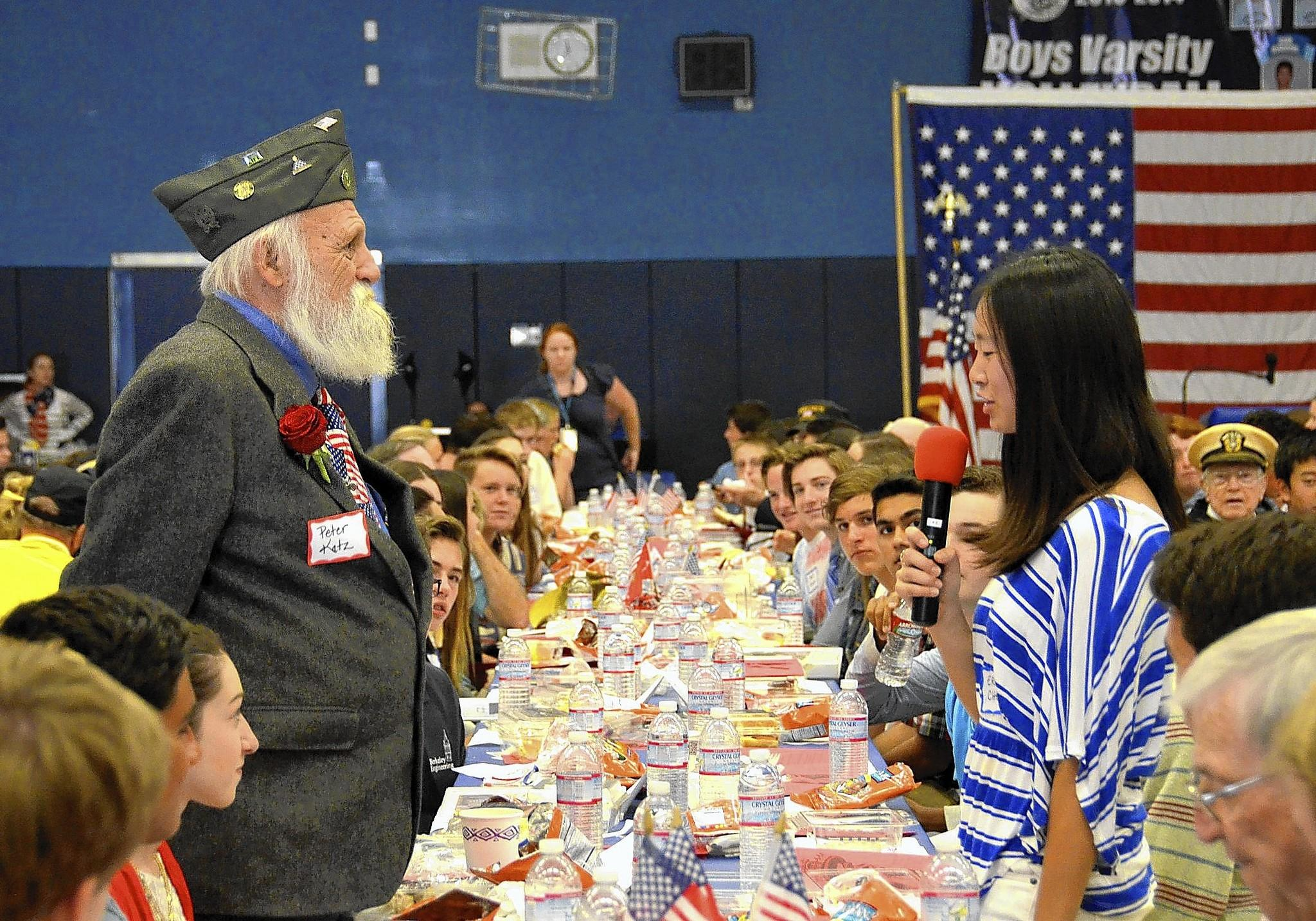 Student Erica Chen, right, introduces proud Army Veteran Peter Katz during the annual Living History Luncheon on Thursday at Corona Del Mar high school.
