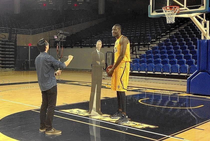 "Wilbert Cheng, a student video producer/director, and Mamadou Ndiaye, UC Irvine's 7-foot-6 center, use a cardboard cutout of Obama as a prop for a video in which Ndiaye says: ""Mr. President, we should play ball together."""