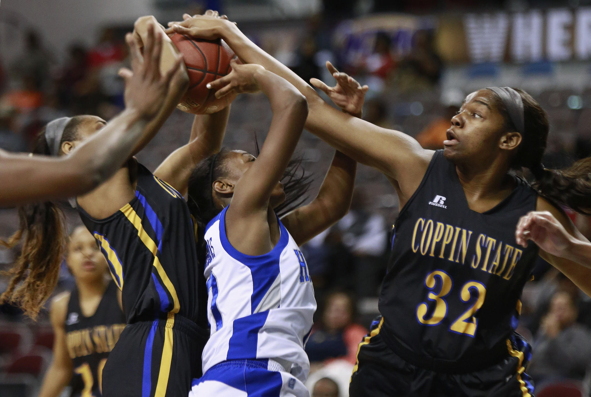 Coppin State's Kyra Coleman, left, and Omaah Tayong block Hampton's Malia Tate-DeFreitas during the first half of the MEAC championship game.