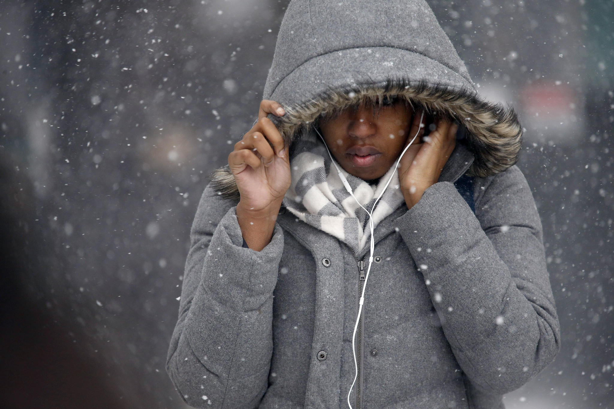 A woman is bundled against the cold and snow.