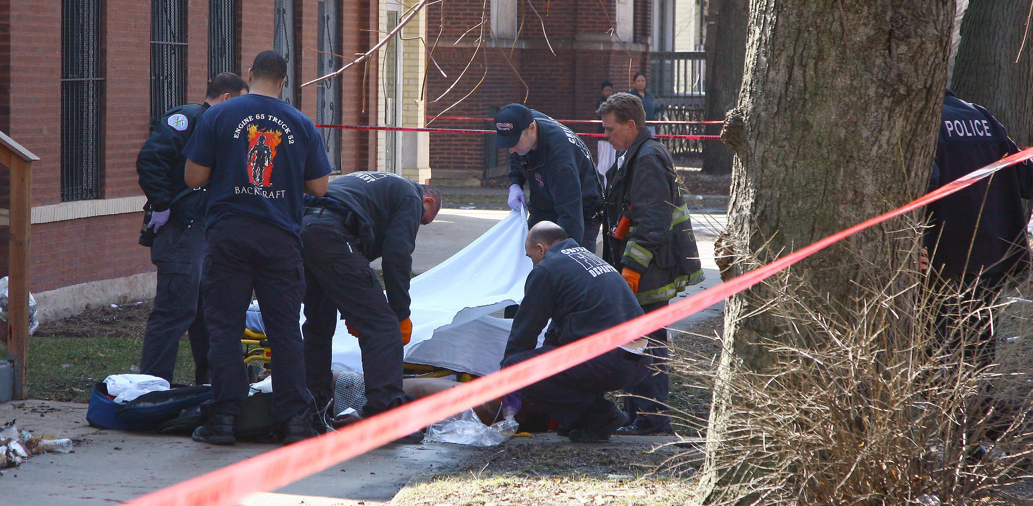 Emergency personnel cover a shooting victim at 69th and Elizabeth Street. The victim was pronounced dead but was later revived at a hospital.