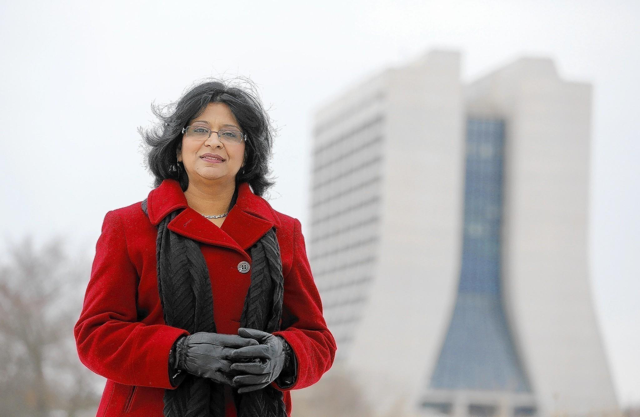"""Portrait of Poonam Gupta-Krishnan, of St. Charles, at Fermi Lab, an IT specialist who launched her own global company, Iyka Enterprises, Inc., and founded the Technology Innovation Summit. Gupta-Krishnan, of St. Charles, is inspired by the work done there, especially those represented by Wilson Hall, at rear, """"It's like a place of worship,"""" she said."""