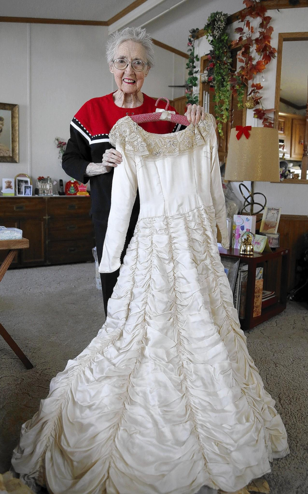 Portrait of Rona Cox, 90, in her southwest suburban home, holds her wedding dress made from parachute silk saved after World War II. She was a corporal in the U. S. Army Air Corps and was married in 1949.