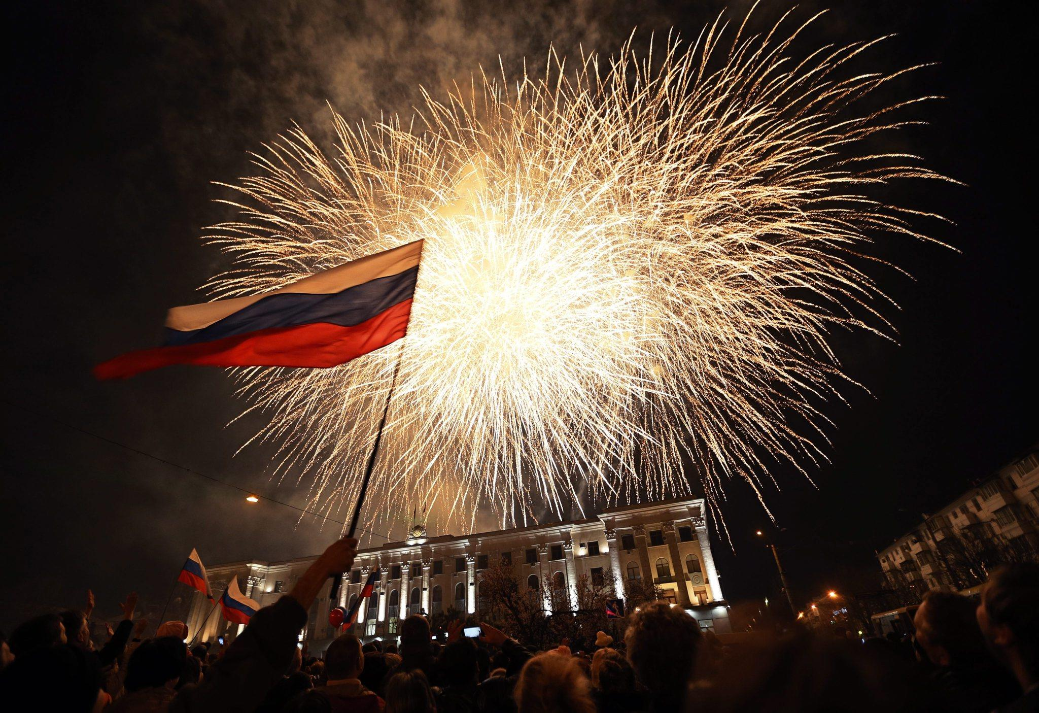 People wave Russian flags as fireworks burst above the central square in Simferopol, the capital of Crimea.