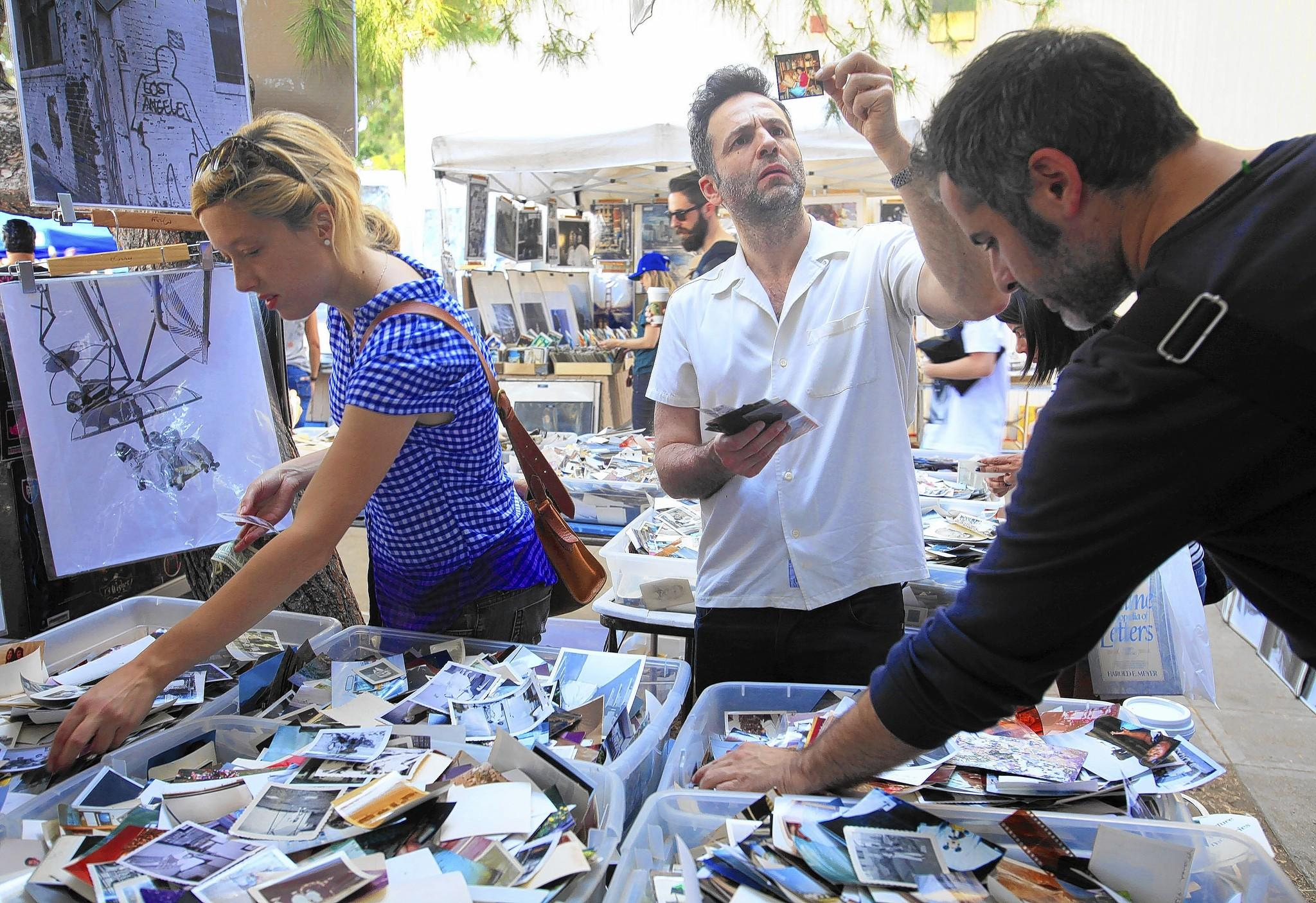 An eclectic aassortment of items awaits visitors to the Melrose Trading Post at Fairfax High School. The flea market includes artwork, glass and, for intrigued shoppers like Gustavo Salmeron, center, bins full of castoff photographs.