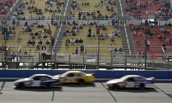 A sparse crowd watches a rain-delayed NASCAR Sprint Cup race at Auto Club Speedway in February 2008. Auto Club Speedway officials announced Friday they are reducing grandstand seating at the race track.