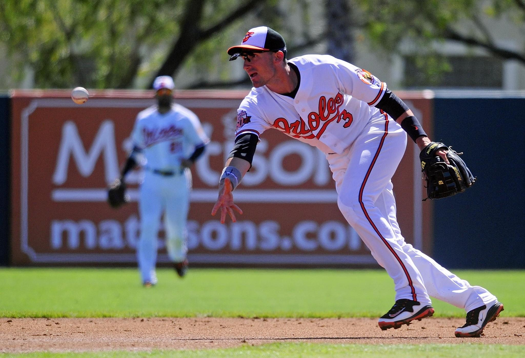 Orioles second baseman Ryan Flaherty flips the ball int he second inning against the Toronto Blue Jays on March 1.