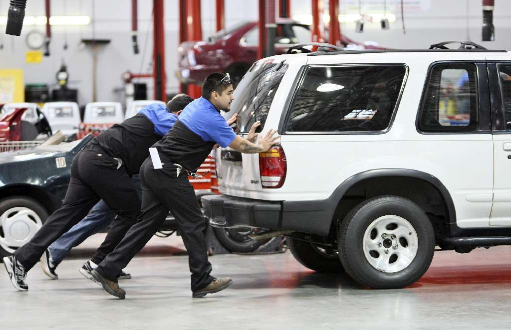 Students are seen pushing a Ford Explorer onto a lift in an automotive technology class at Corinthian Colleges' WyoTech campus in Long Beach. The Obama administration is trying to prevent federal aid from going to schools whose non-degree program students have high default rates.