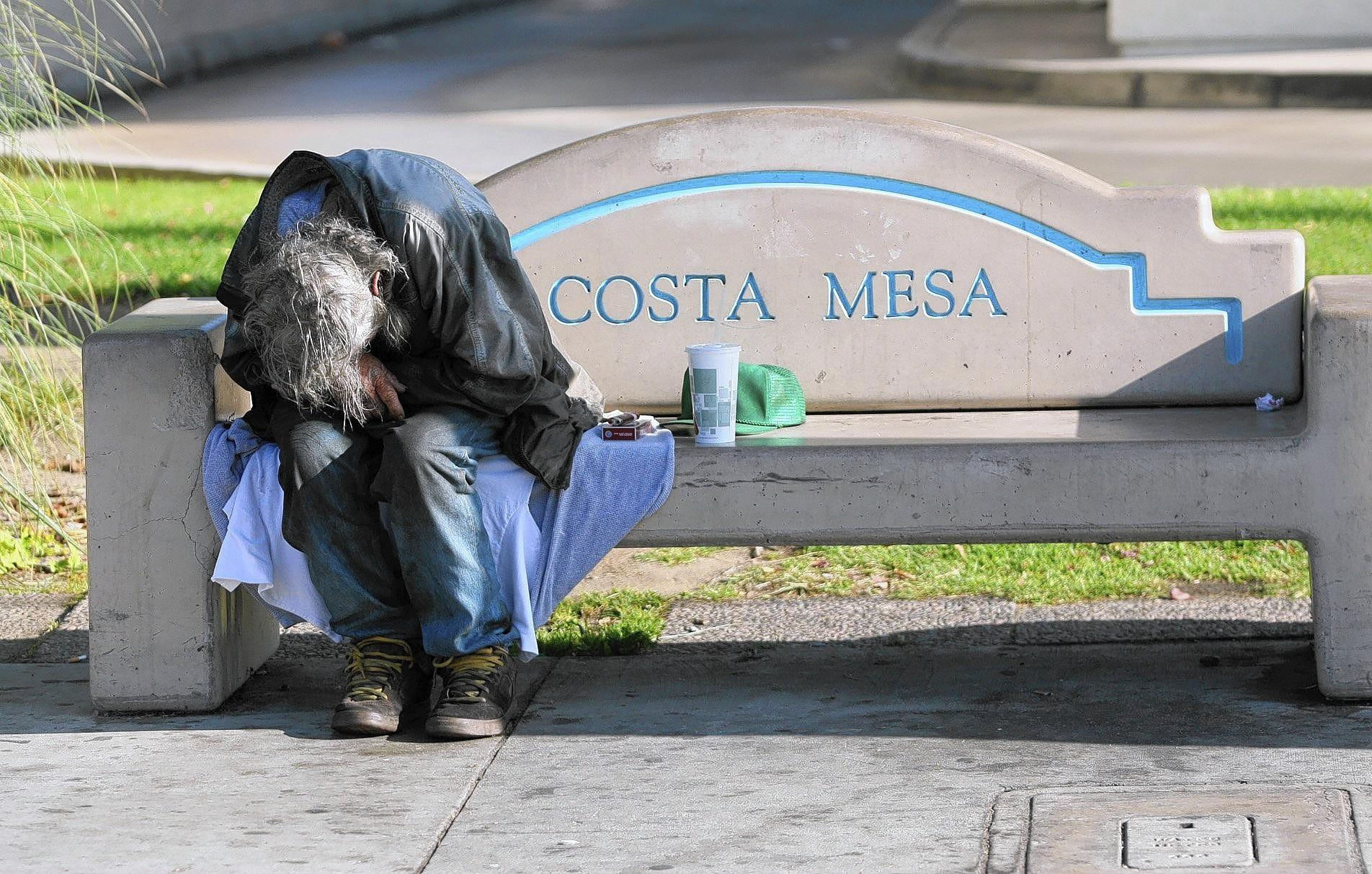 A homeless man sleeps on a bench near Wilson Street and Harbor Boulevard.