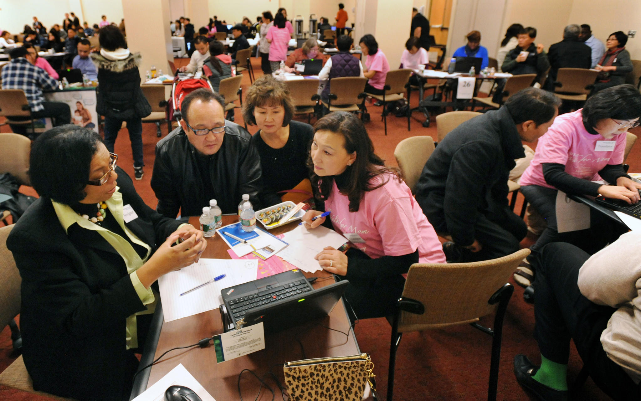 Counselors help Korean Americans sign up for health insurance during an event at Holy Name Medical Center in Teaneck, N.J., this month.