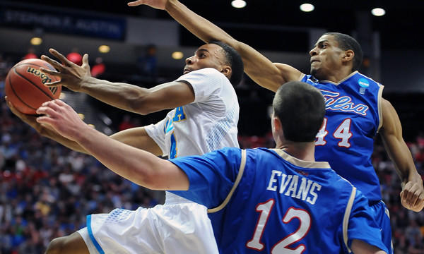 UCLA's Norman Powell, left, drives between Tulsa's Brandon Swannegan, top right, and Lew Evans during the first half of the Bruins' 76-59 win in the second round of the NCAA tournament Friday.