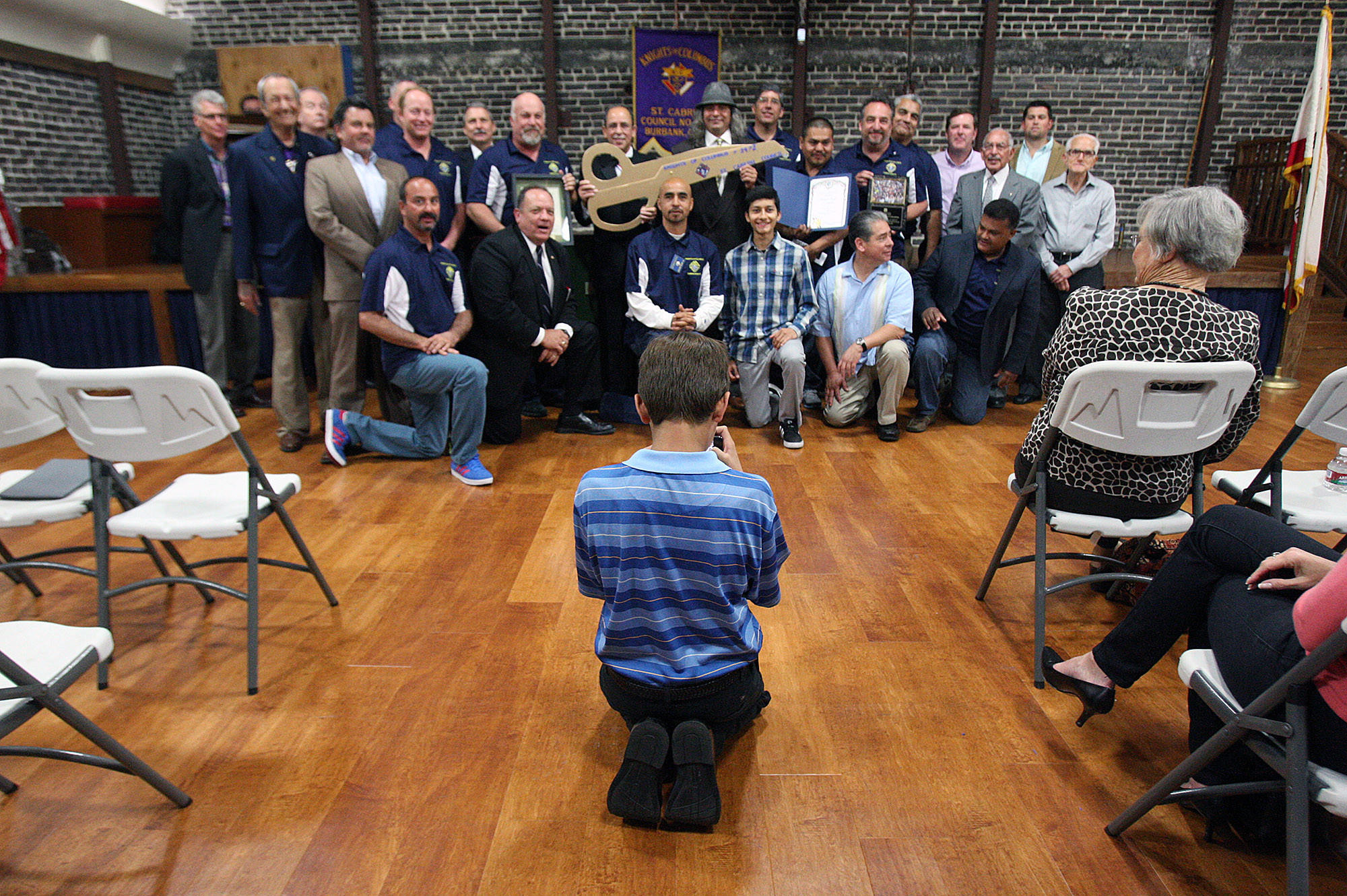 Anthony Chiaravalle, 11, of Burbank, takes a group photo with his iPhone of the Knights who attended the first meeting, and hall rededication ceremony of the Knights of Columbus Saint Cabrini Council in Burbank on Friday, March 21, 2014 since the fire that destroyed the adjacent building and damaged their building in May, 2013.