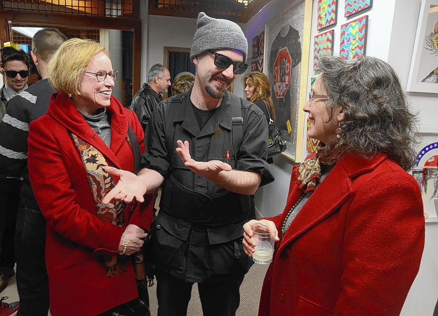 Jacob Pongratz, (center) owner of Pongratz Fine Art shares a moments with Martha Ahlquist (left) and Laura Green (right) during an art show opening reception at Pongratz Fine Art Friday evening. More than dozen artists participate in the show