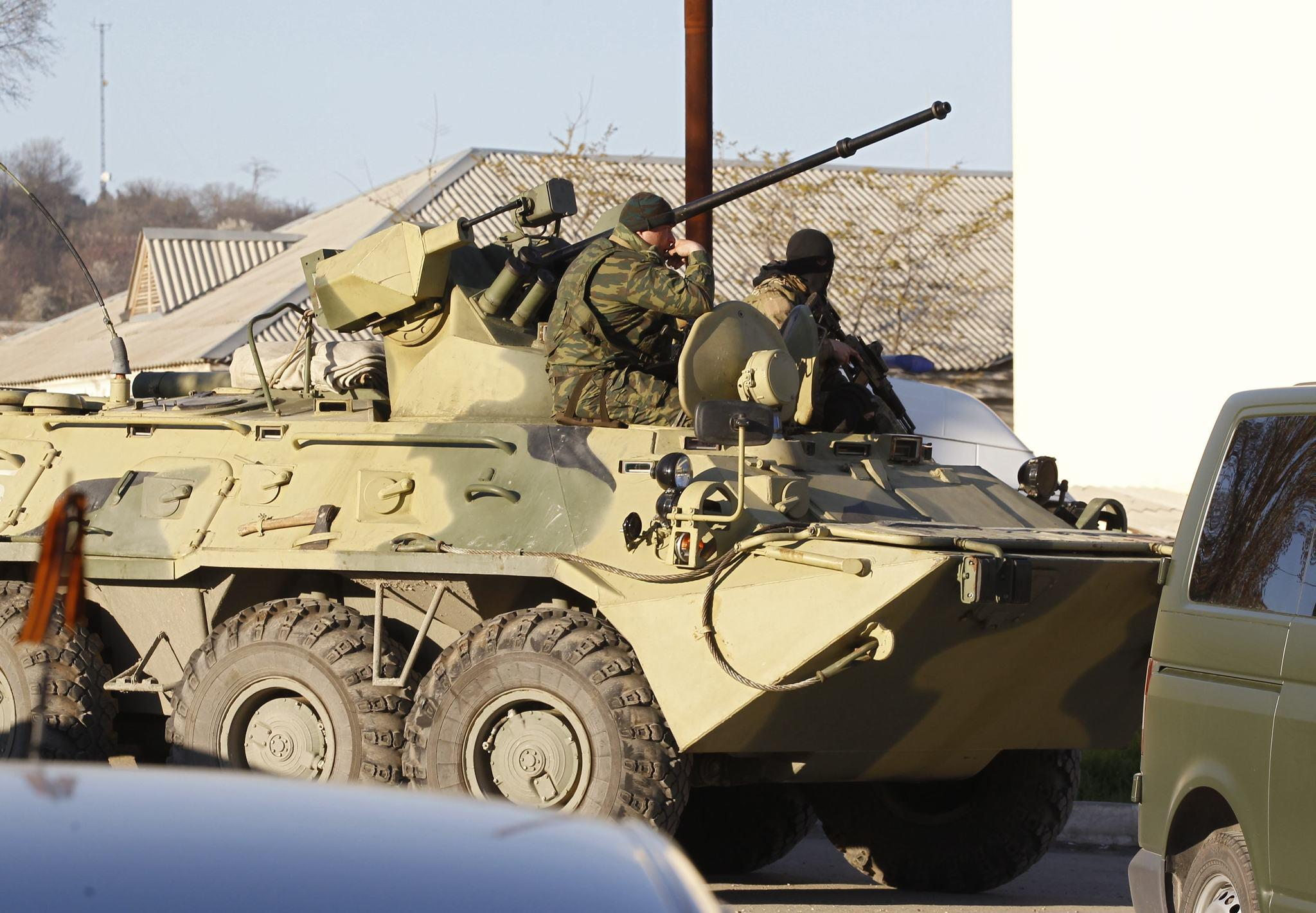 Armed men, believed to be Russian servicemen, sit in an armoured vehicle near a military base in the Crimean town of Belbek near Sevastopol on March 22. Russian troops have surrounded a Ukrainian airbase in Crimea and issued an ultimatum to forces inside to surrender.