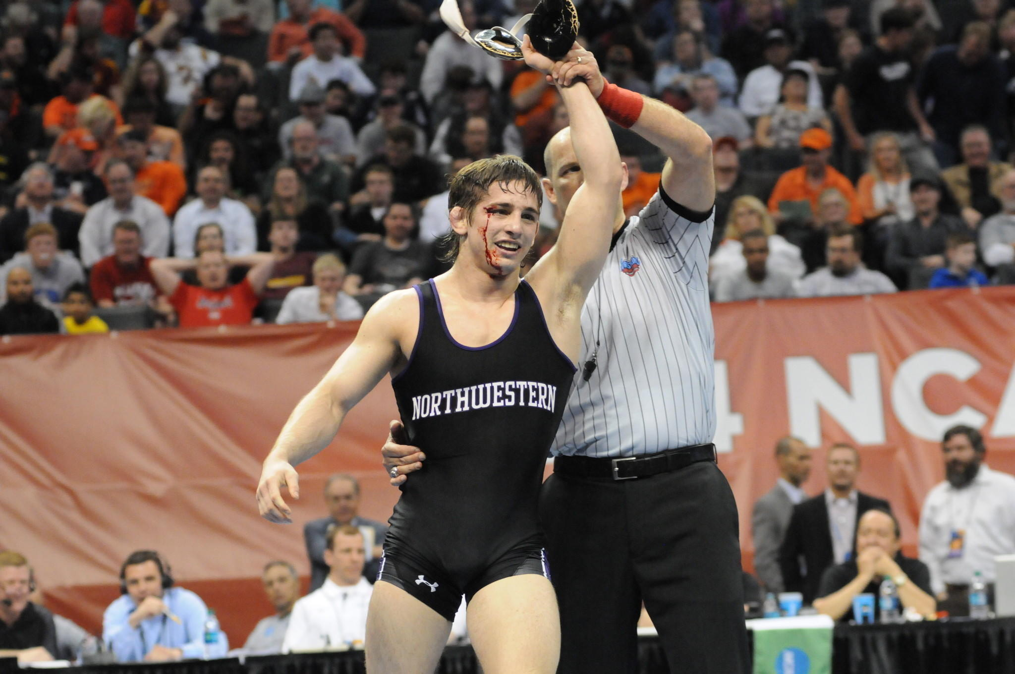 Bloodied but unbowed: Jason Tsirtsis after winning his NCAA wrestling semifinal.