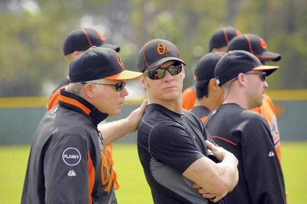 Baltimore Orioles special assistant Brady Anderson leans back to listen to manager Buck Showalter on the first day of spring training at the Orioles' training facility Feb. 19, 2012.