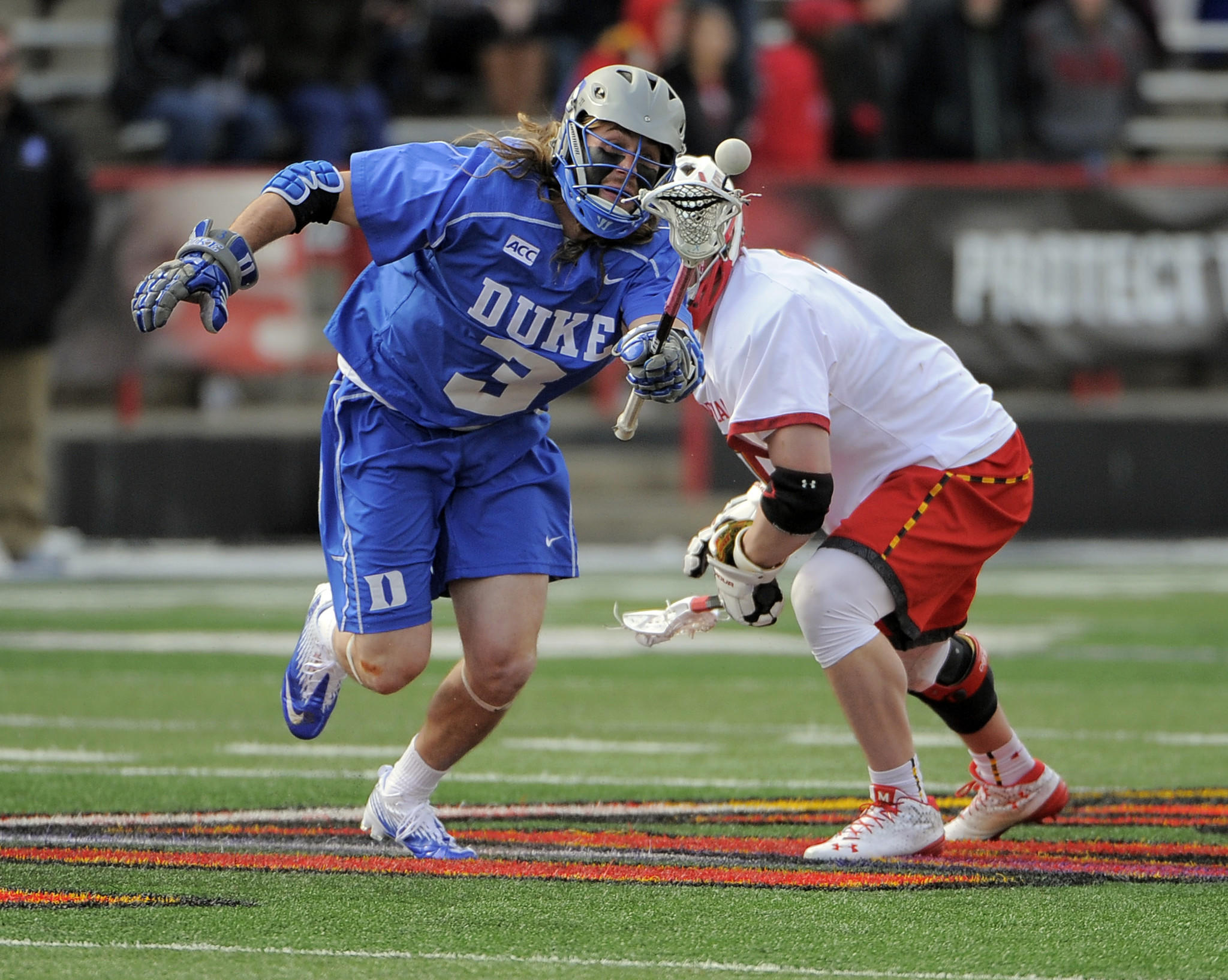 Duke's Brendan Fowler pops the ball to himself after beating Maryland's Charlie Raffa on a third-quarter faceoff.