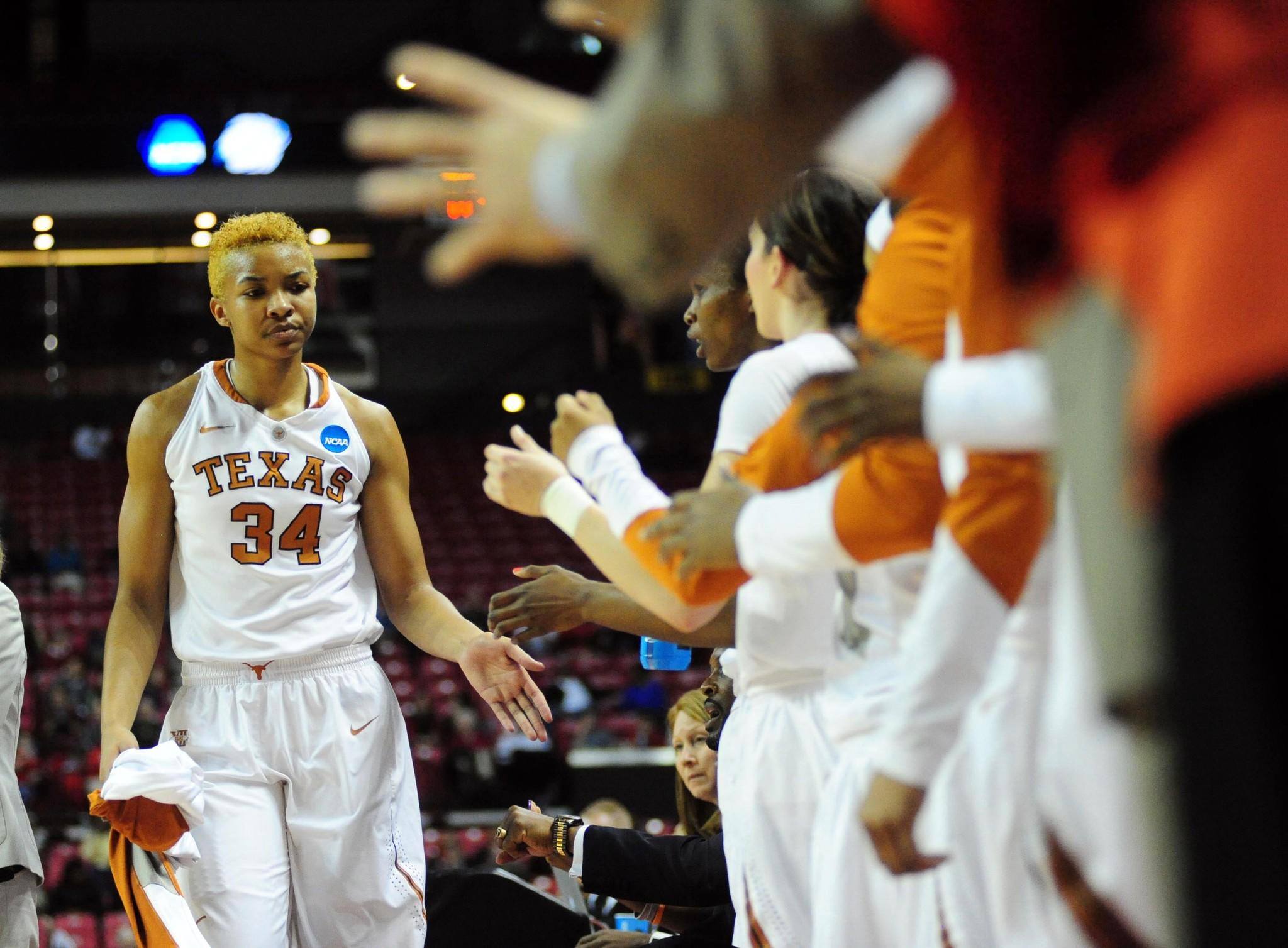 Imani McGee-Stafford high fives teammates after coming out in the first half of Texas' NCAA tournament win over Penn on Sunday at Comcast Center.