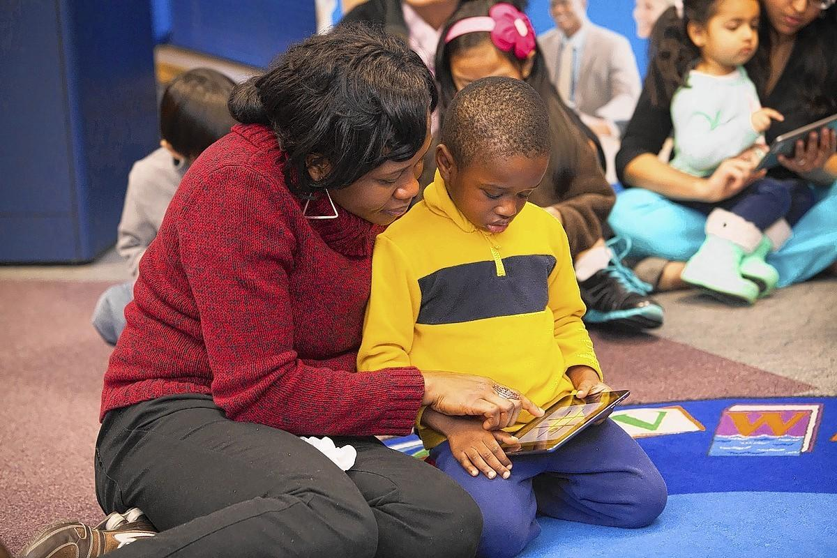 Chioma Nwafor and her son, Kelechi Nwafor, use the iPad mini during the Little Leapers 3.5 kickoff.