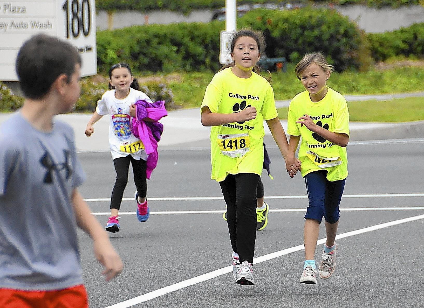 Two College Park students hold hands as they race to the finish line during the 31st annual Newport Mesa Spirit Run held at Fashion Island on Sunday.