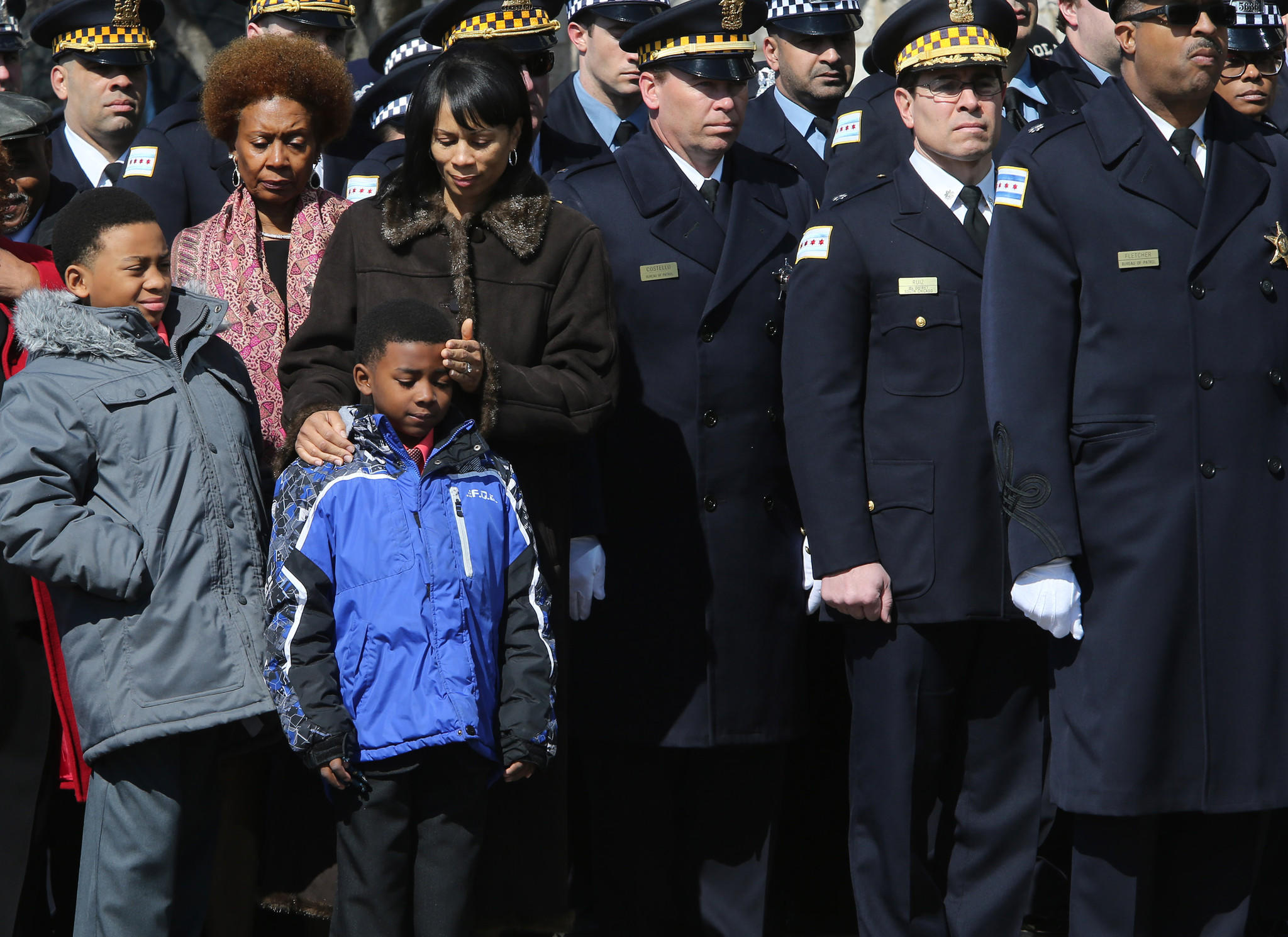 Widow Sandra Harris stands with sons Caleb Emmanuel Harris, blue jacket, and David Lee Harris III, left, as police officers gather outside Living Word Christian Church in Forest Park Monday for the funeral service of Police Officer David Harris.