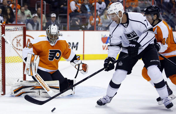 Kings forward Jeff Carter, center, tries to settle the puck in front of Philadelphia Flyers goalie Ray Emery and defenseman Kimmo Timonen, right, during the first period of the Kings' 3-2 road win Monday.