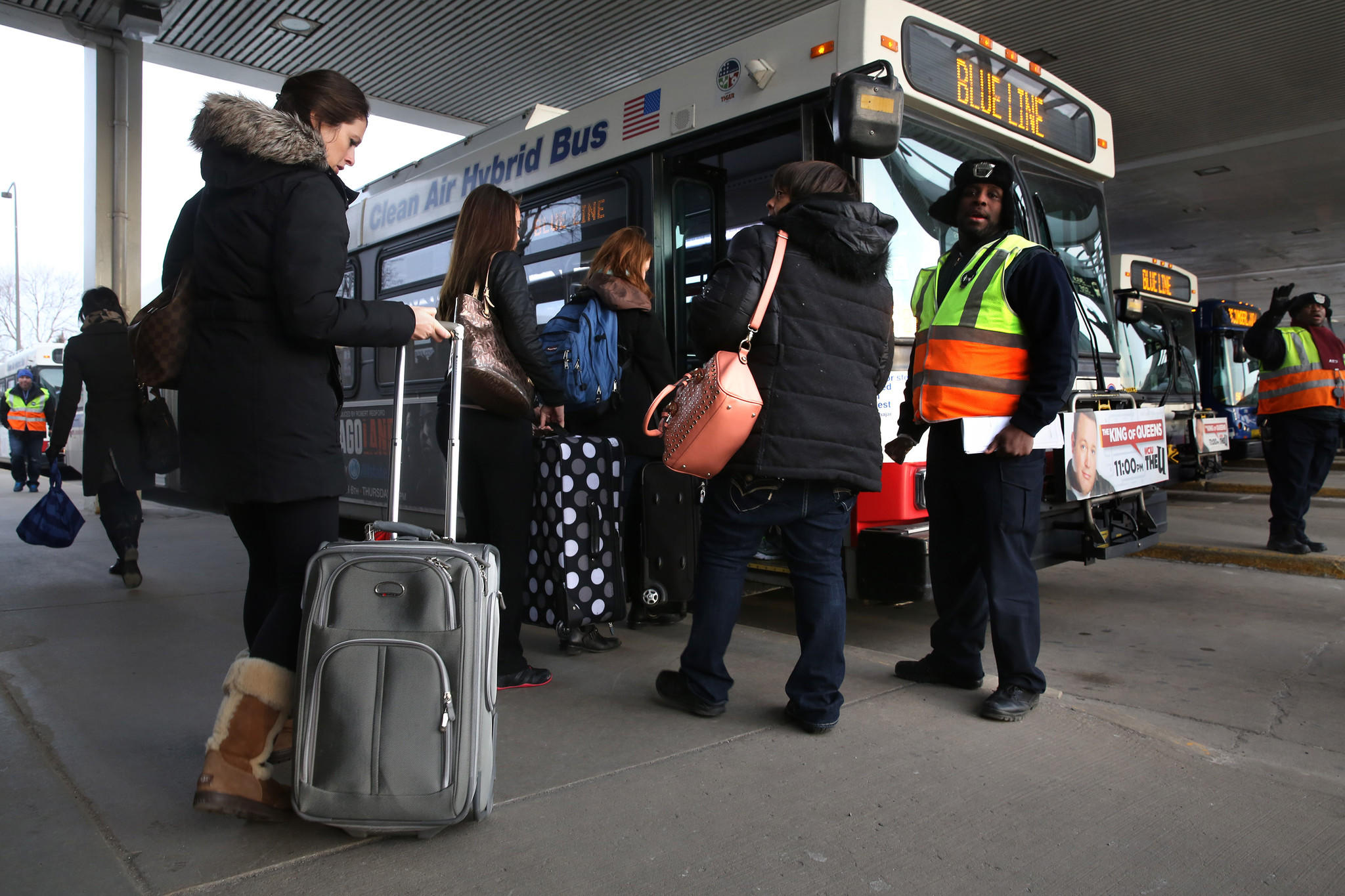 """At the Rosemont """"L"""" station near O'Hare Airport, CTA workers and supervisors direct Blue Line passengers onto shuttle buses to the airport after a CTA train crashed into the O'Hare station and part way up an escalator early Monday."""
