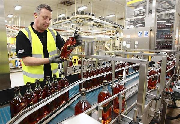 A worker looks at a bottle of Johnnie Walker whisky at the Diageo owned Shieldh