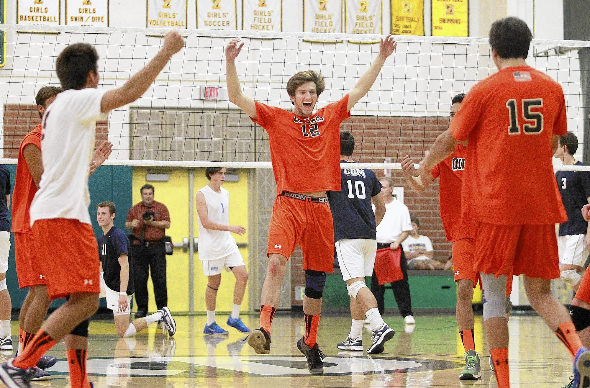 Huntington Beach High's Drake Evans (12) celebrates a big point with teammates against Corona del Mar at Edison High on Monday.
