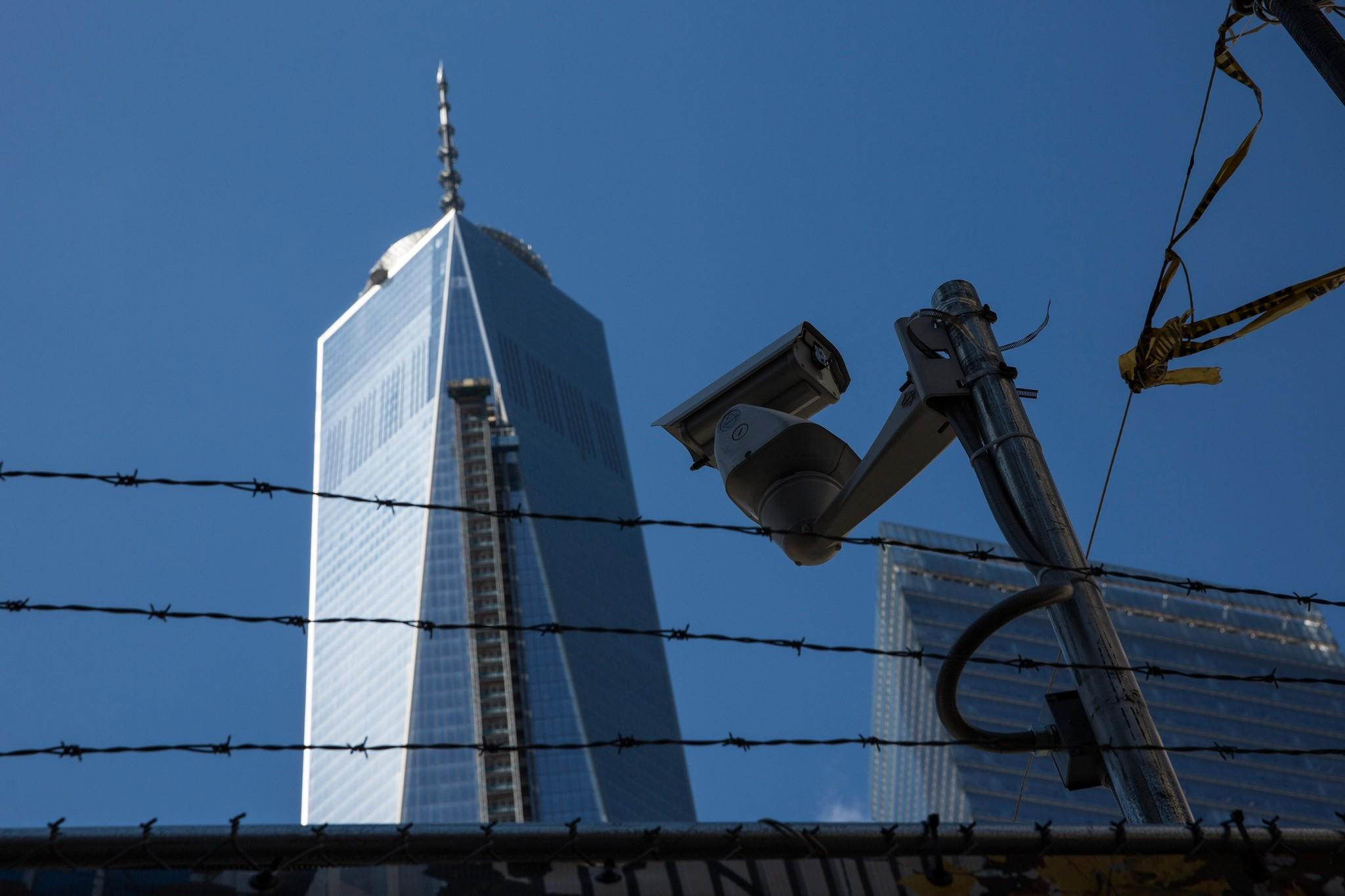 A security camera is positioned next to a barbed wire fence outside Ground Zero and One World Trade Center in New York City on March 21.